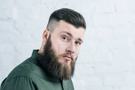 portrait of handsome bearded man in shirt against white brick wall