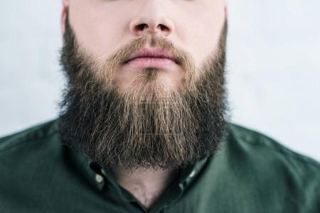 Foto de Recortar foto de hombre con barba en la camiseta contra la pared de ladrillo blanco - Imagen libre de derechos