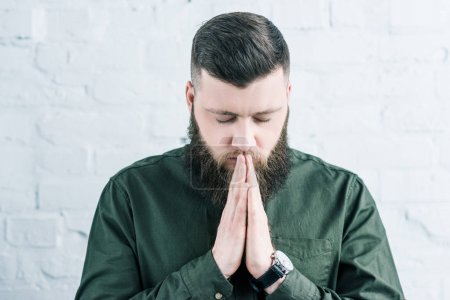 portrait of stylish bearded man praying against white brick wall