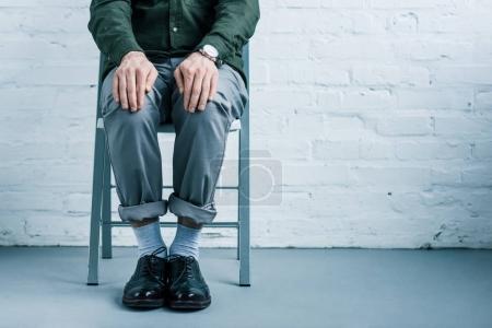 Foto de Vista parcial del hombre de negocios sentado en silla contra la pared de ladrillo blanco - Imagen libre de derechos