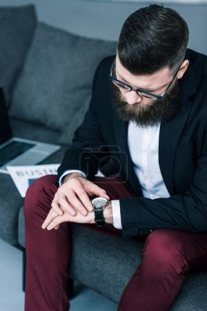 selective focus of businessman checking time while sitting on sofa with laptop and business newspaper