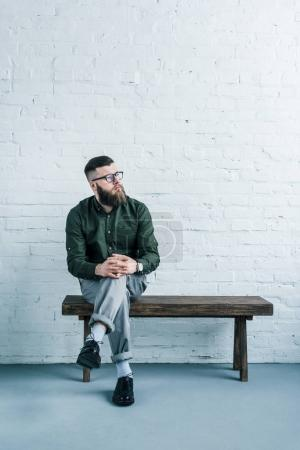 pensive businessman sitting on wooden bench against white brick wall