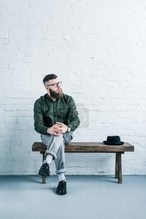 pensive businessman sitting on wooden bench with hat against white brick wall