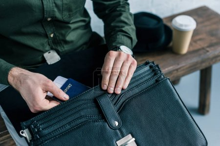cropped shot of businessman putting passport and ticket into suitcase