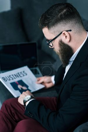 selective focus of businessman with newspaper in hand checking time