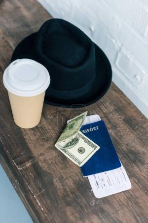close up view of arranged passport, cash, coffee to go and hat on wooden bench
