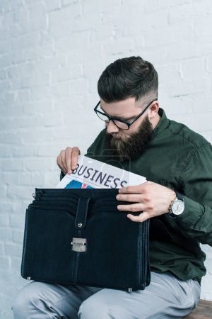 portrait of bearded businessman in eyeglasses putting business newspaper into suitcase