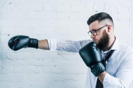 side view of bearded businessman in eyeglasses and boxing gloves against white brick wall