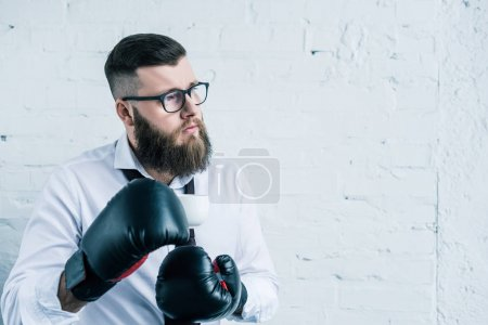 portrait of pensive businessman in boxing gloves holding cup of coffee