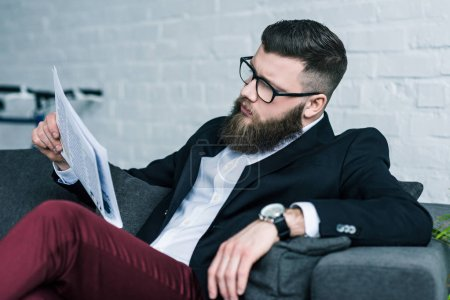 stylish bearded businessman resting on sofa and reading newspaper