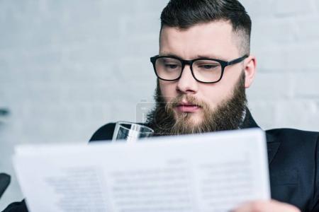 selective focus of focused businessman in eyeglasses reading newspaper