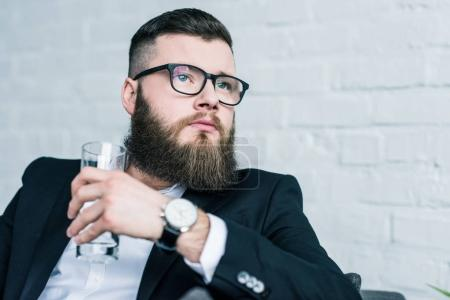 portrait of pensive businessman with glass of water in hand looking away