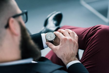 partial view of businessman checking time