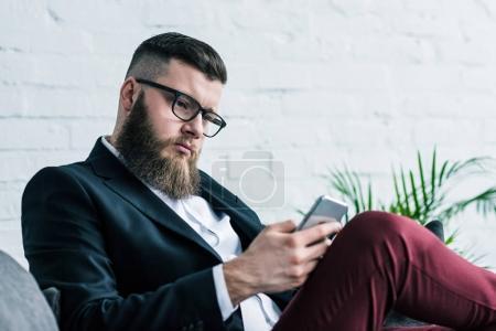 Photo for Stylish focused businessman using smartphone - Royalty Free Image