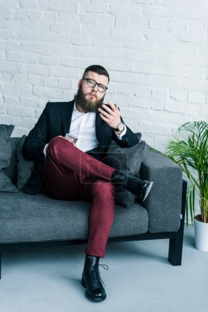 Photo for Bearded businessman in suit with smartphone in hand resting on sofa - Royalty Free Image