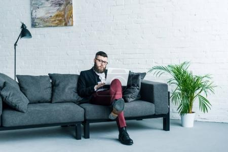 bearded businessman in stylish suit sitting on sofa and using laptop