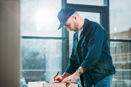 Courier checking cardboard box and cargo declaration