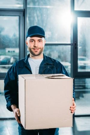 Young courier holding cardboard box