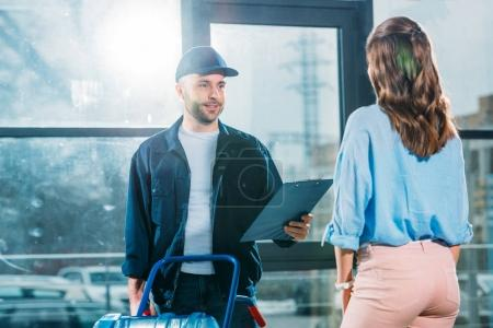Photo for Woman receiving water delivery from courier - Royalty Free Image