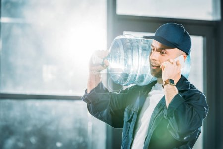 Delivery guy carrying water bottle and talking on phone
