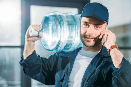 Photo pour Chargeur transportant la bouteille d'eau et de parler au téléphone - image libre de droit