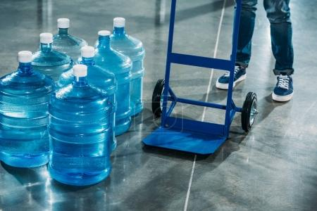 Photo for Courier with delivery cart standing by water bottles - Royalty Free Image