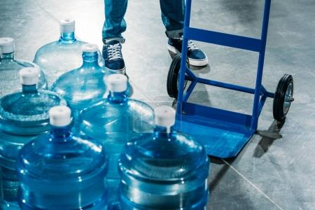 Loader man with delivery cart standing by water bottles