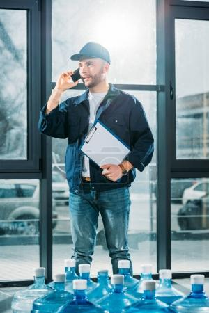 Delivery man with clipboard talking on a phone