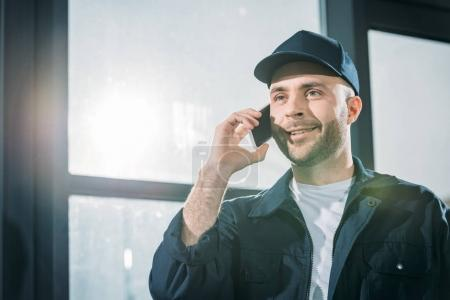 Smiling courier making a phone call