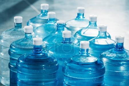 Plastic large blue water bottles on floor