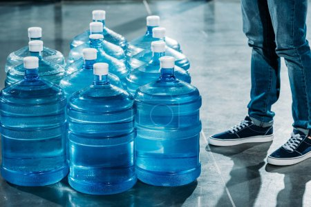 Courier standing by large bottles with drinking water