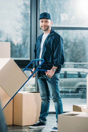 Delivery man pushing hand truck with boxes