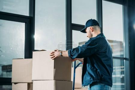Courier stacking cardboard boxes on handcart