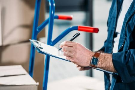 Close-up view of delivery man filling cargo declaration