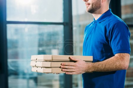 Close-up view of delivery guy holding pizzas in boxes