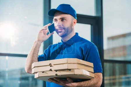 Courier with pizzas in boxes making phone call