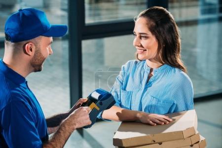 Photo pour Femme tenant des pizzas dans des boîtes en messagerie réglage terminal de paiement - image libre de droit