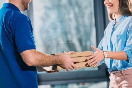 Woman receiving pizzas in boxes from delivery man