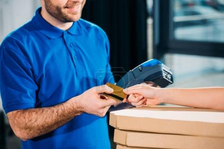 Woman holding stack of pizzas in boxes and passing card for carrier with payment terminal