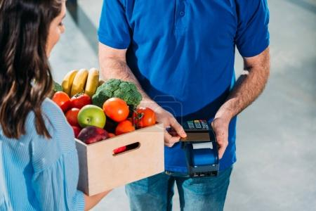 Delivery man using card and payment terminal while woman holding groceries in box