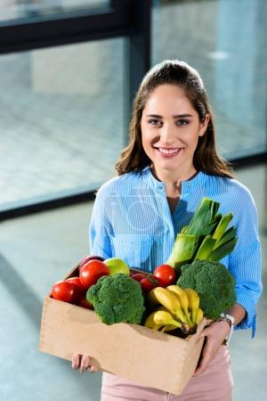 Smiling woman holding box with fresh fruits and vegetables