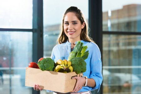 Smiling woman holding box with groceries