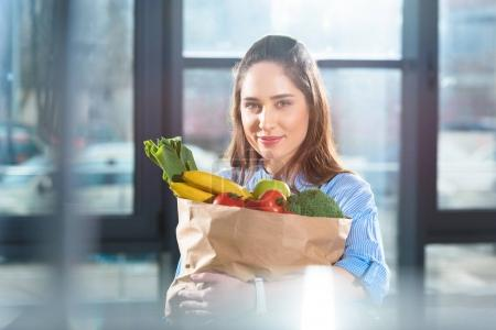 Smiling woman holding paper bag with fresh fruits and vegetables
