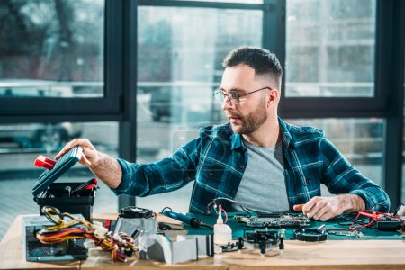 Hardware engineer with instruments and circuit board at workplace