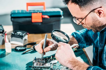 Hardware engineer looking at circuit board through magnifying glass