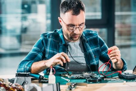 Photo for Repairman testing circuit board with multimeter - Royalty Free Image