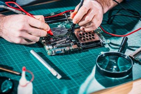 Photo pour Vue rapprochée de la carte de circuit d'essai mâle ingénieur - image libre de droit
