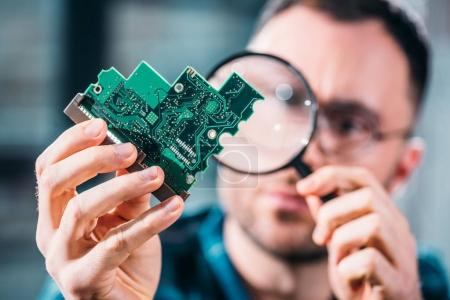 Photo for Close-up view of man looking at circuit board through magnifying glass - Royalty Free Image
