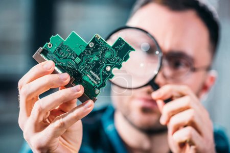 Close-up view of man looking at circuit board through magnifying glass