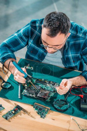 Top view of engineer in glasses working with pc parts